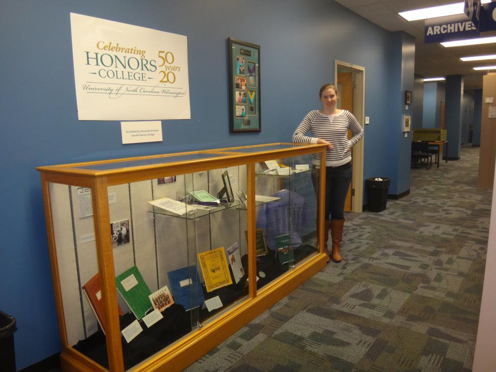 Graduate Assistant Beth Bullock standing next to the Honors exhibit.