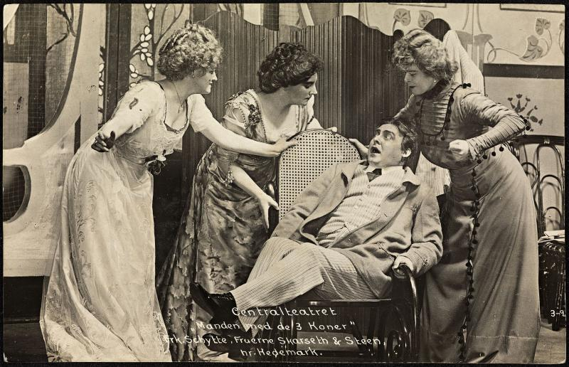 Three women stand around a man in a chair. All in period costumes. Antique postcard.