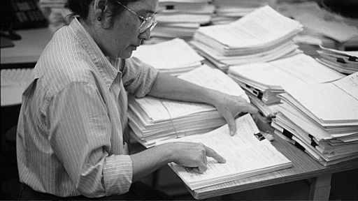 A woman wearing glasses reads a document. There are mounds of paper on the desk in front of her.