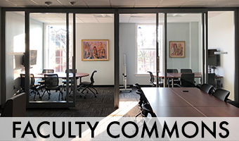 The inside of the faculty commons, with desks, tables and chairs.